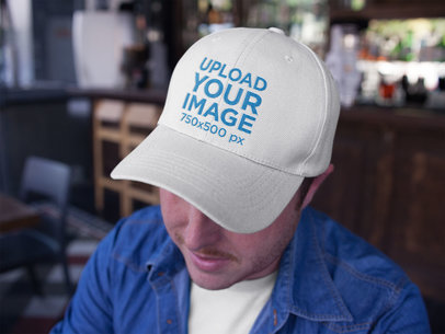 Closeup Mockup Featuring a Dad Hat Being Worn by a Guy at the Bar a15888