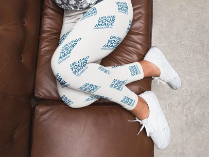 Girl Legs Wearing Leggings Mockup and White Shoes on a Brown Sofa a15706