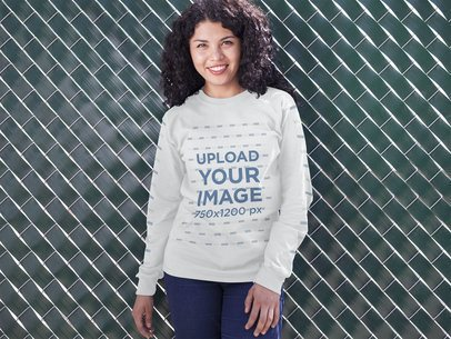 Mockup of a Young Girl Wearing a Crewneck Sweatshirt while Standing Against a Green Fence Outdoors a15975