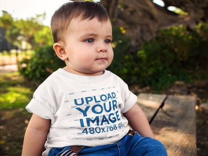 Little Baby Boy Wearing a Round Neck Tee Mockup While Sitting Down Outdoors a16102