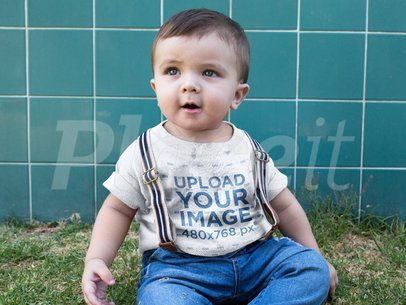 Little Baby Boy Wearing a Round Neck Tee Mockup While Sitting Down in the Grass 16083