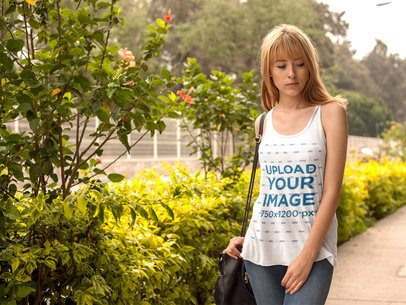 Mockup of a Blonde Woman Wearing a Bella Canvas Tank Top in a Garden a16111