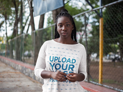 Front Shot Mockup of a Black Girl with Dreadlocks Wearing a Heather Long Sleeve Tee Mockup While in a Basketball Court a16199