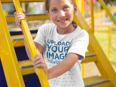 Happy Little Girl Wearing a Round Neck Tee Mockup While on Yellow Stairs Outdoors a16159