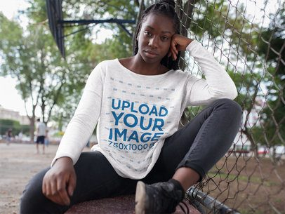 Woman Wearing a Round Neck Long Sleeve Heather Tee Template While Sitting Down Outdoors Against a Fence a16201