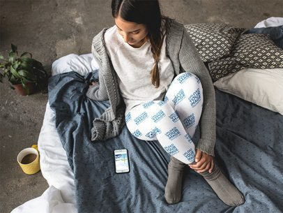 Woman Wearing Leggings Template While Sitting Down at Home Near her Phone a15708