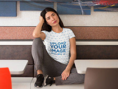 Pretty Girl Sitting Down in a Restaurant While Wearing a Sublimated Tee Mockup a16129
