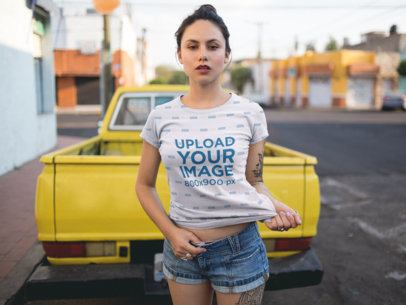 Young Woman Wearing a Round Neck Tee Mockup While Against a Yellow Pick Up Truck in the Street a15434