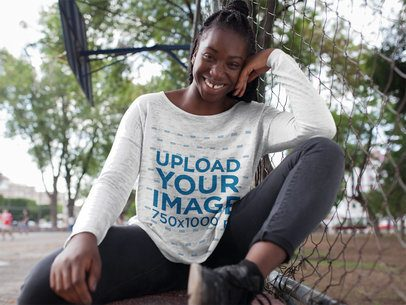 Young Black Happy Woman with Dreadlocks Wearing a Bella Flowie Long Sleeve Off Shoulder Tee Mockup While Crouching Outdoors a16202