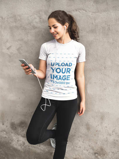 Girl Listening to Music Against Concrete Wall While Wearing Custom Activewear Mockup a16863