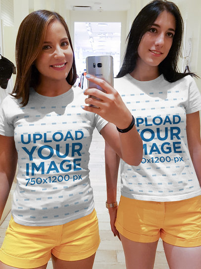 Two Girls Taking a Selfie Against a Mirror Wearing Round Neck Tees Mockup at a Fitting Room a16923
