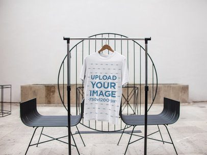 T-Shirt Mockup on a Hanger Inside a White Room a16946