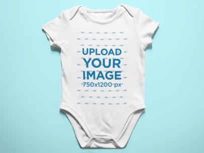 Baby Onesie Lying On A White Surface Mockup a14054
