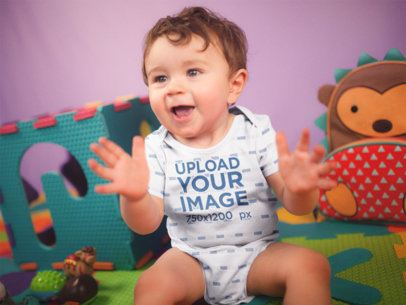 Happy White Baby Boy Clapping While Sitting Down Wearing A Onesie Mockup a16972