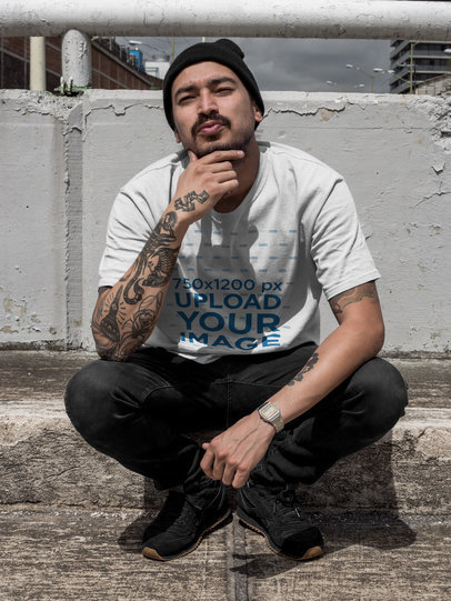 Chilling Tattooed Man Wearing a Round Neck Tee Mockup While Squatting on a Bridge a17075