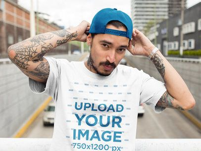 Tattooed Man at a Bridge Wearing a T-Shirt Mockup While Fitting his Hat a17082