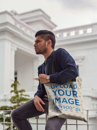 Hispanic Man Sitting Down Near a White House While Carrying a Tote Bag Mockup a17087