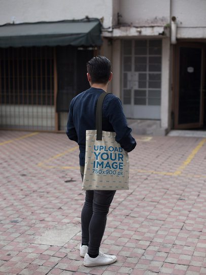 Young Man Carrying a Tote Bag Mockup from the Back a17089