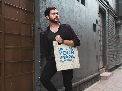 Attractive Man Carrying a Tote Bag Mockup While Against a Wall in an Alley a17090