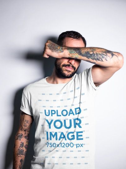 Tattooed Man Covering his Face While Wearing a T-Shirt Mockup a17025
