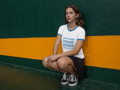 Woman Sitting Against a Wall While Wearing a Ringer Tshirt Mockup a17062
