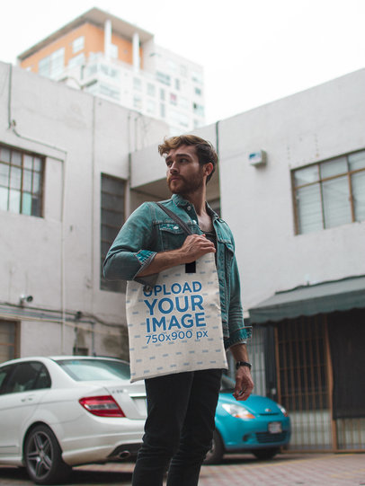 Man Wearing a Denim Jacket Carrying a Tote Bag Mockup While Outdoors a17091