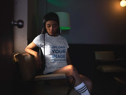Mockup of a Pretty Girl Wearing a Tshirt While in a Low Lit Room a17204