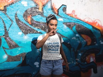 Girl with a Bandana Wearing a Tee Mockup While Making a Horns Sign Against a Graffiti Wall a17205