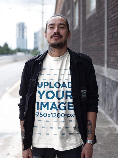 Tattooed Man Wearing a Tshirt Mockup and a Black Jacket While Walking on the Street a17080
