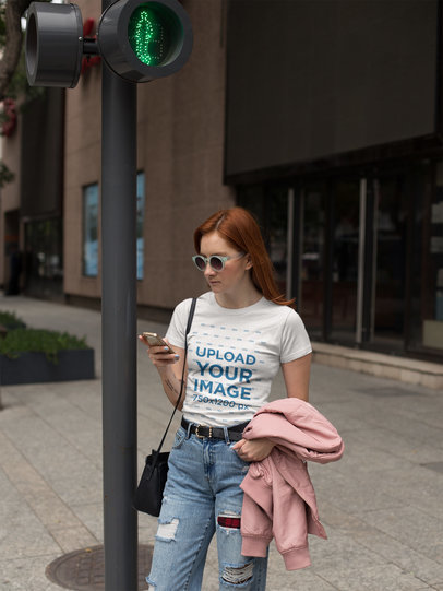 Girl Wearing a Tshirt Mockup While Using her Phone Crossing the Street a17250