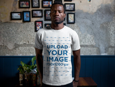 Tshirt Mockup of a Man Standing Against a Wall with Framed Pictures a17168