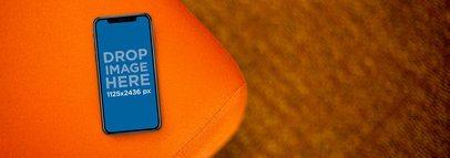 iPhone X Mockup Lying on the Corner of an Orange Sofa a17377