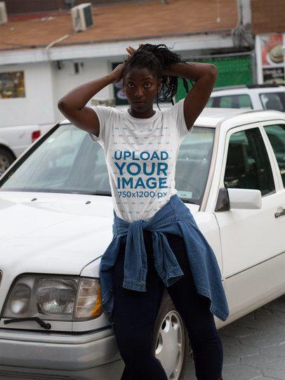 Black Girl with Dreadlocks Wearing a T-Shirt Mockup While Walking Near a Car a17327