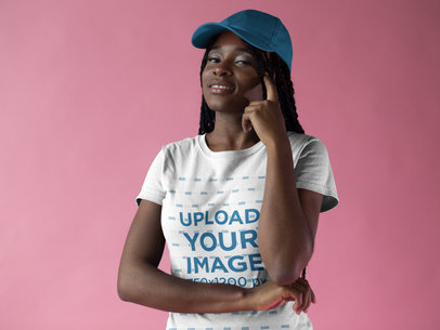 Smiling Black Girl Wearing a Round Neck Tee Mockup and a Hat Against a Pink Background a17195