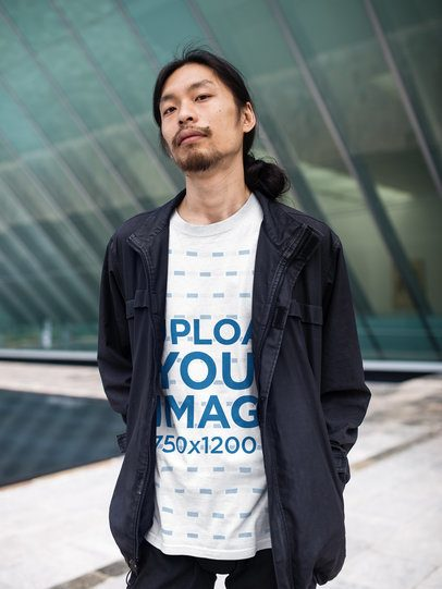 Asian Man Wearing a Round Neck T-Shirt Mockup While Outside a Urban Structure sa17785