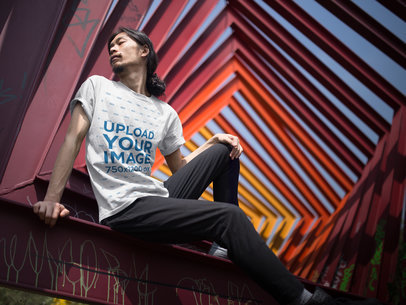 Long Hair Asian Man Wearing a T-Shirt Mockup While Sitting on a Red Urban Structure a17823