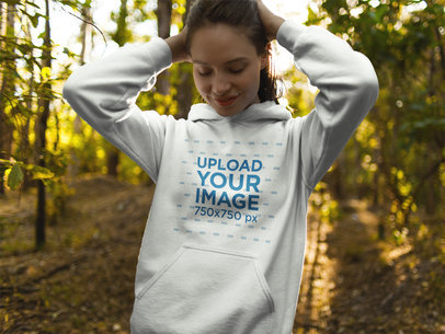 Girl Wearing a Hoodie Mockup While in the Woods a17906