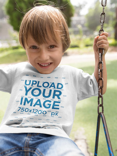 Little Boy Wearing a T-Shirt Mockup While on a Swing a17939