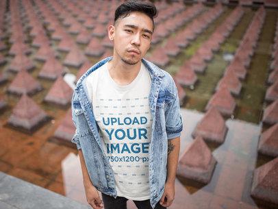 Cool Asian Man Wearing a T-Shirt Mockup and a Denim Jacket Near an Urban Structure a17830