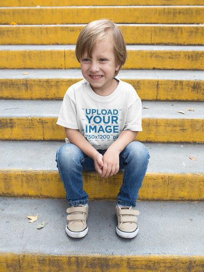 Happy Kid Wearing a Tshirt Mockup while Sitting on Yellow Concrete Stairs a17947