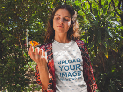 Girl Holding a Butterfly Wearing a Tshirt Mockup Near Plants a18458