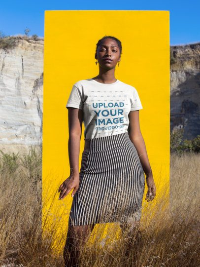 Beautiful Woman Standing Against a Yellow Rectangle Wearing a Tshirt Mockup a18570