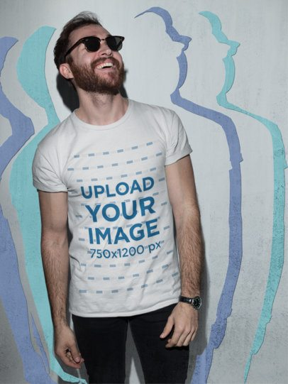 Cool Shot of a Happy Dude with a Beard Wearing a Tshirt Mockup Against a Concrete Wall a18699