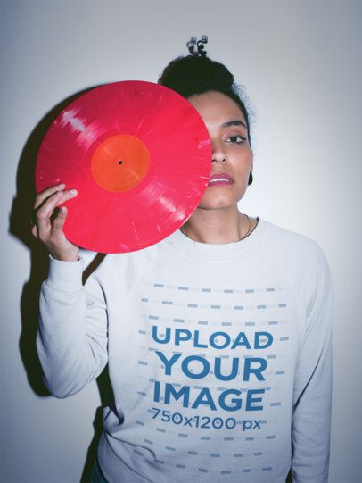Serious Girl Wearing a Crewneck Sweatshirt Mockup Holding a Pink Vinyl Against her Eye a18836
