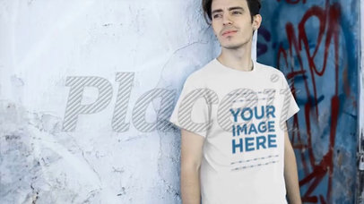 Video of a Young Man Wearing a Tshirt Lying Against an Old Wall a12863