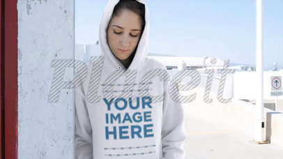 Video of a Girl Wearing a Hoodie Mockup Leaning Against a Wall a13190