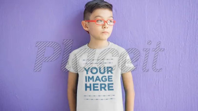 Video of a Young Asian Boy with Glasses Standing in Front of a Purple Wall Wearing a Kid's Tee a12539