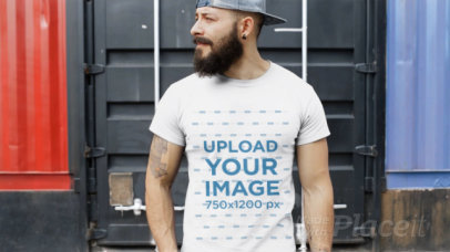 Tattooed Guy Wearing a Hat and Round Neck Tee Video Mockup in a Container Yard a12263