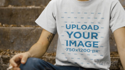 Dude Wearing a T-Shirt Video Sitting on a Concrete Stairway a12862