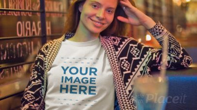 Young White Woman Wearing a T-Shirt Video Mockup at a Coffee Shop at Night a13405